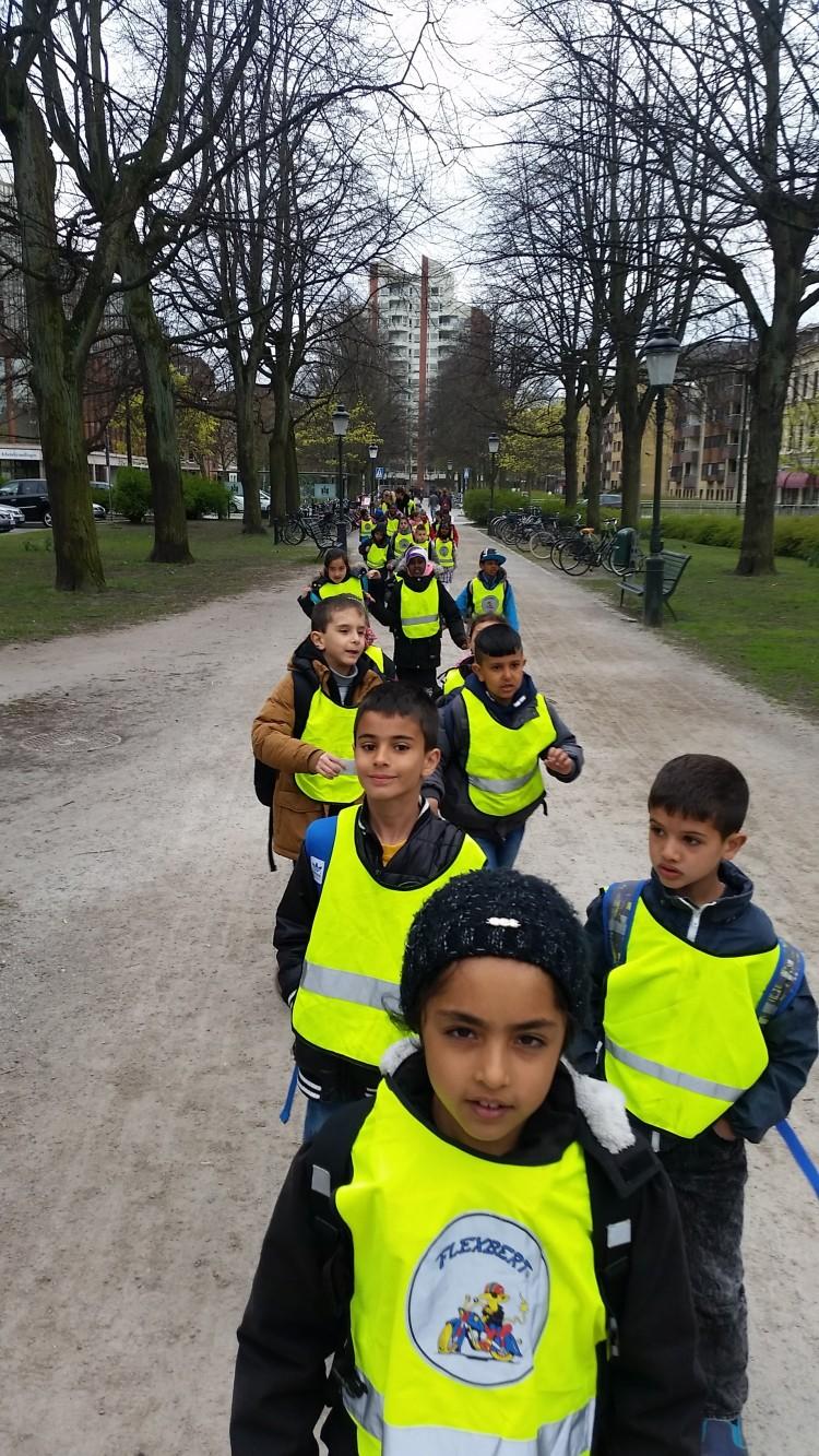 Barn i reflexvästar promenerar längs med Kungsgatan i Malmö.