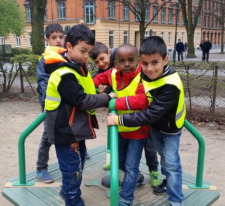Barn i reflexvästar i lekpark.