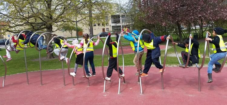 Barn i reflexvästar på lekpark.