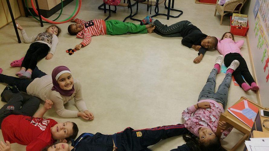 Barn ligger i en cirkel på golvet.