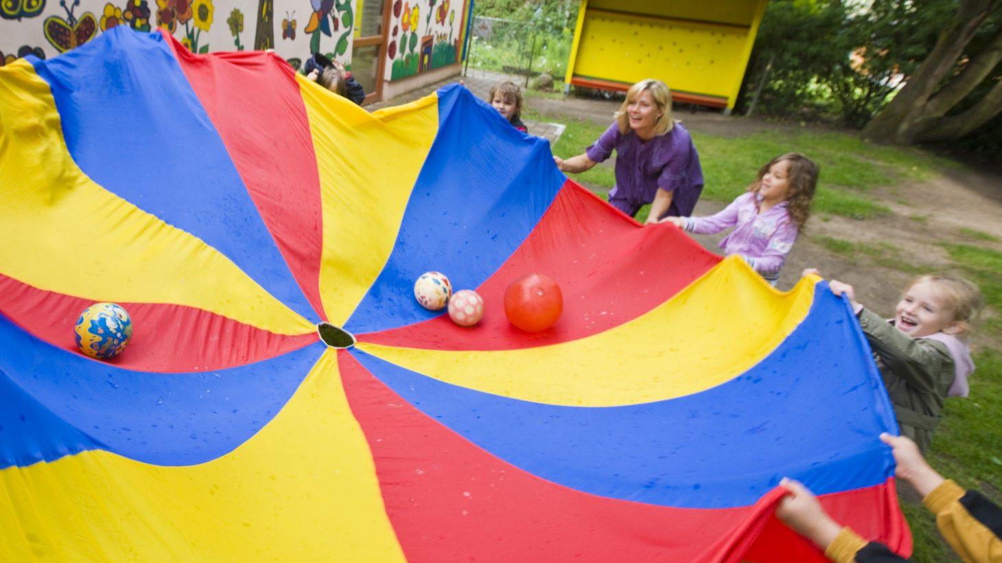 Pedagog och barn håller upp stor runt tygstycke med bollar i mitten.