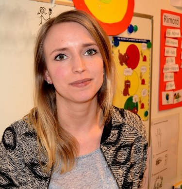 Kvinna framför tavla i klassrum.