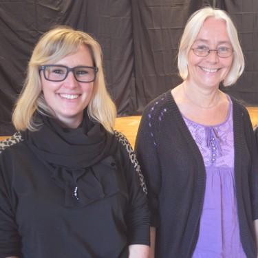 Två kvinnor framför en scen.