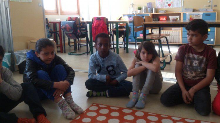 Barngruppen sitter på golvet.