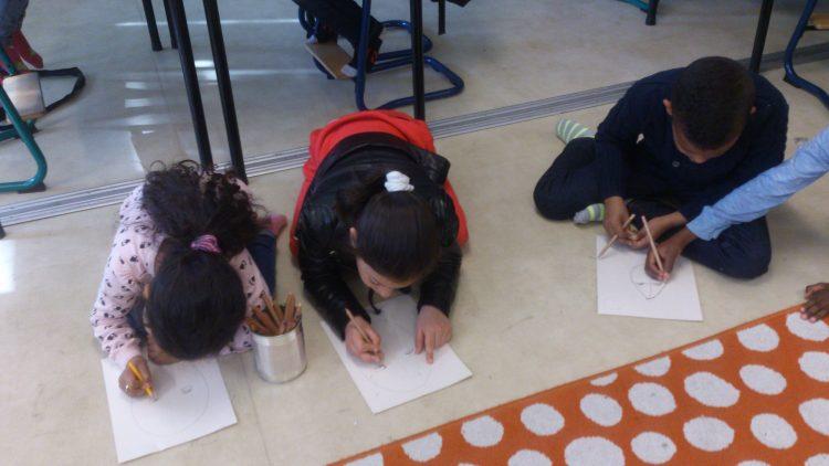 Elever sitter på golvet och ritar.