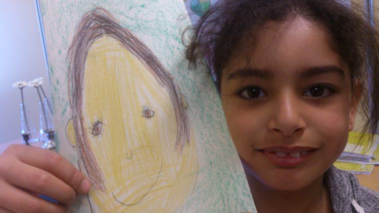 Elev håller upp sitt porträtt.
