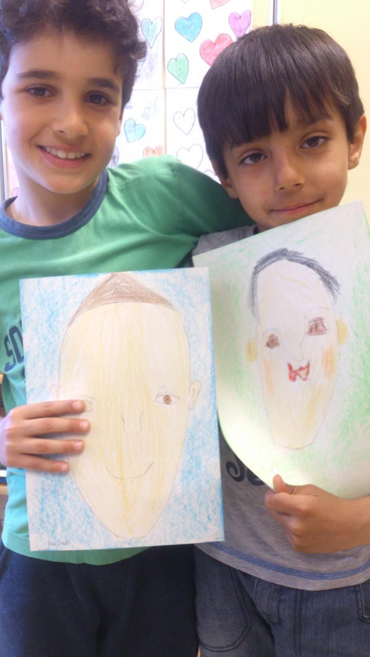 Två elever håller upp sina porträtt.