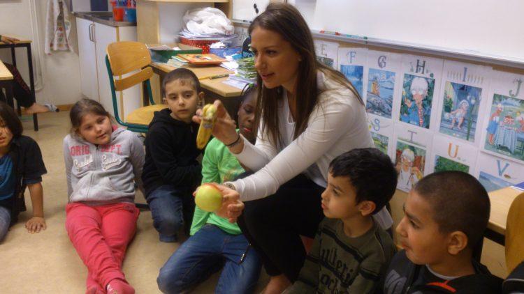 Lärare håller fram äpple och banan till eleverna.