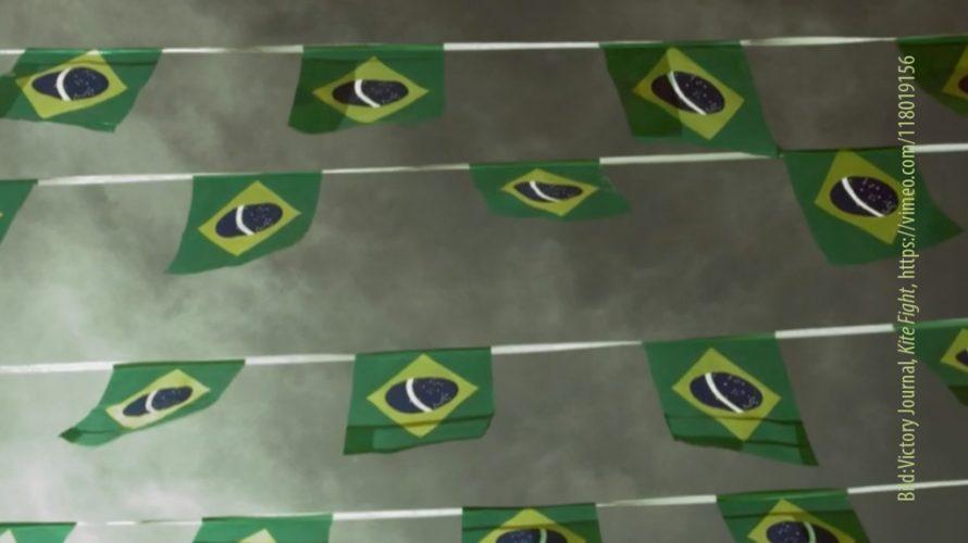 Flera exemplar av Brasiliens flagga hänger mot en grå himmel.