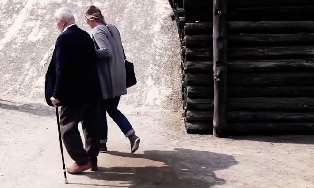 Kvinna stödjer äldre man med käpp.