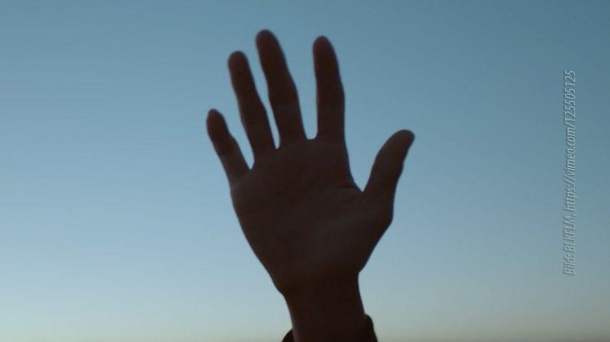 Hand hålls upp i motljus.