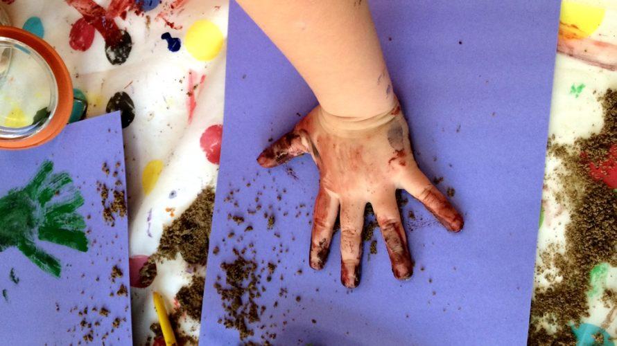 Barnhand full av målarfärg gör handavtryck.