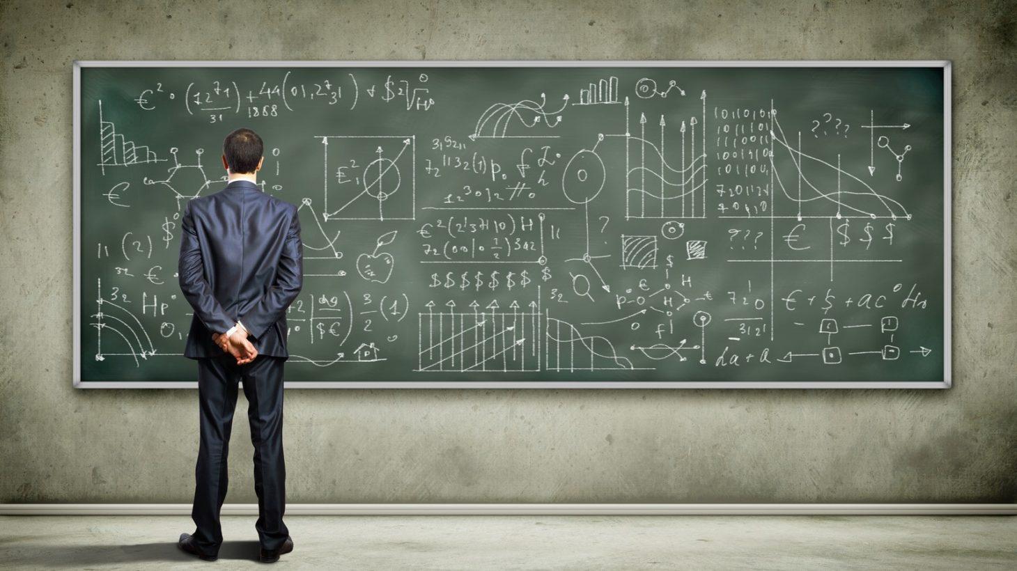 Man står framför grön tavla fylld av ekvationer och diagram.