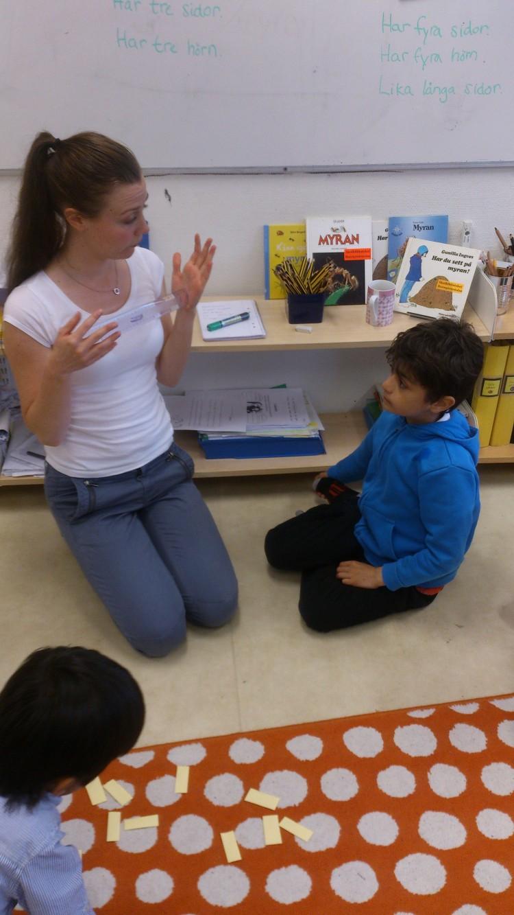 Pedagog visar upp linjal för elev.