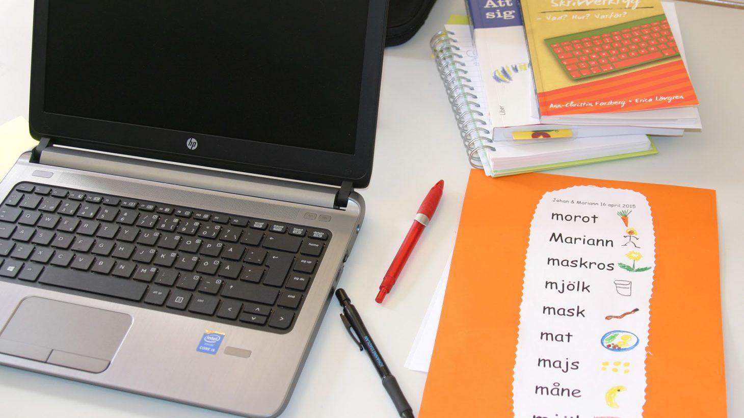 Ordlista ligger bredvid laptop.