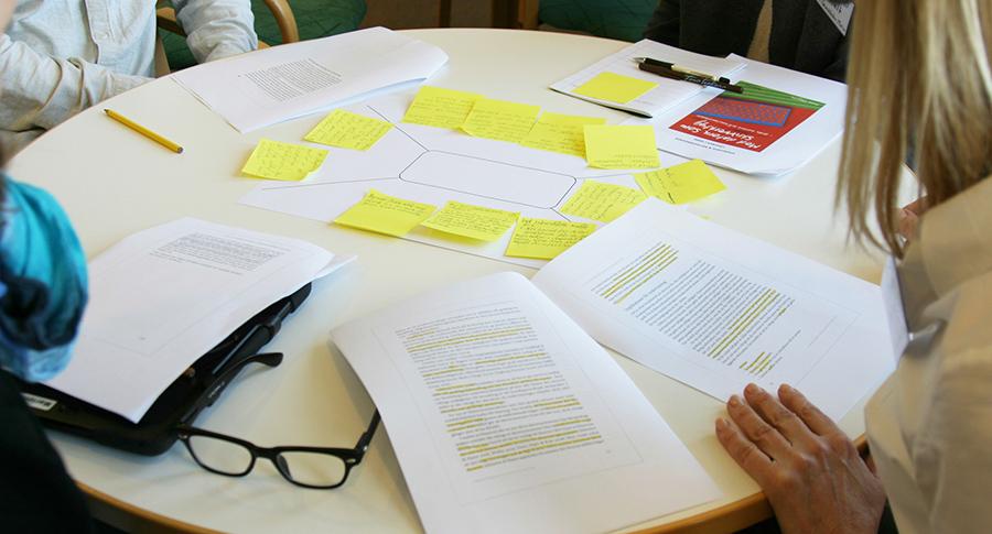 Anteckningspapper och kompendium ligger på ett bord.