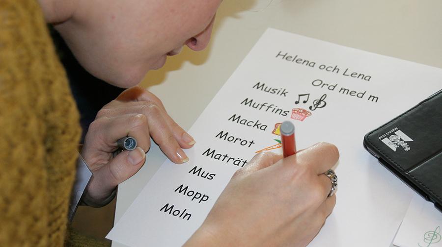 Person ritar på papper där det står ord på m.