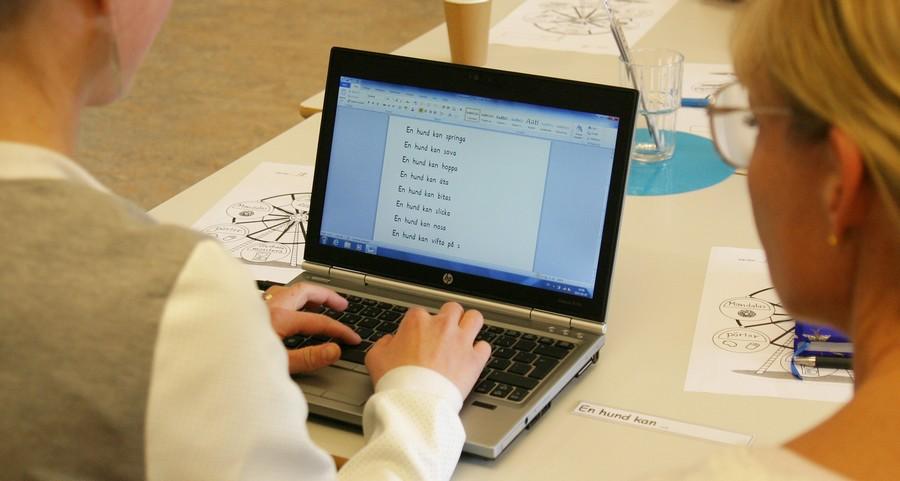 Person skriver på tangentbord på uppfälld laptop.
