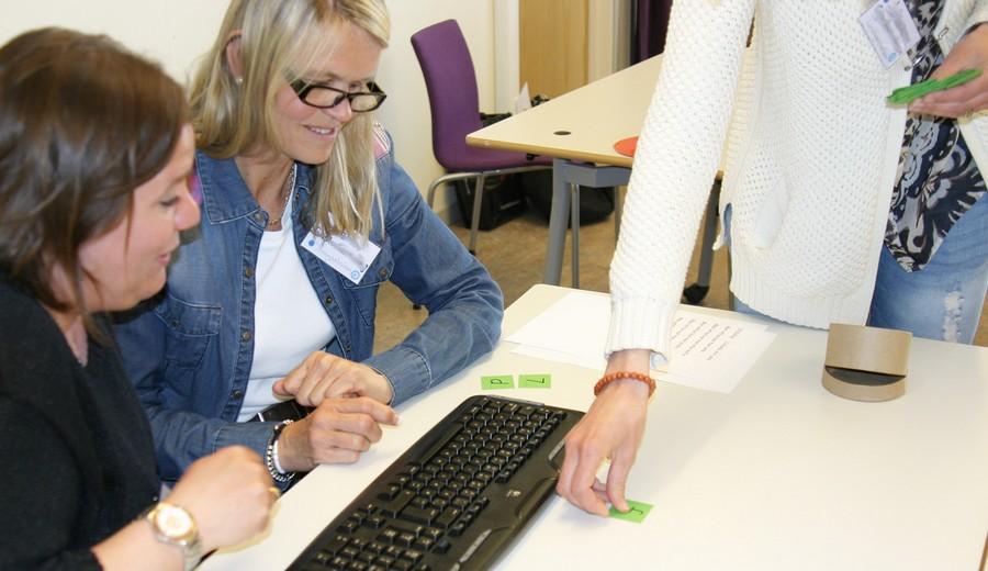Grön lapp delas ut till två kvinnor som sitter vid tangentbord.