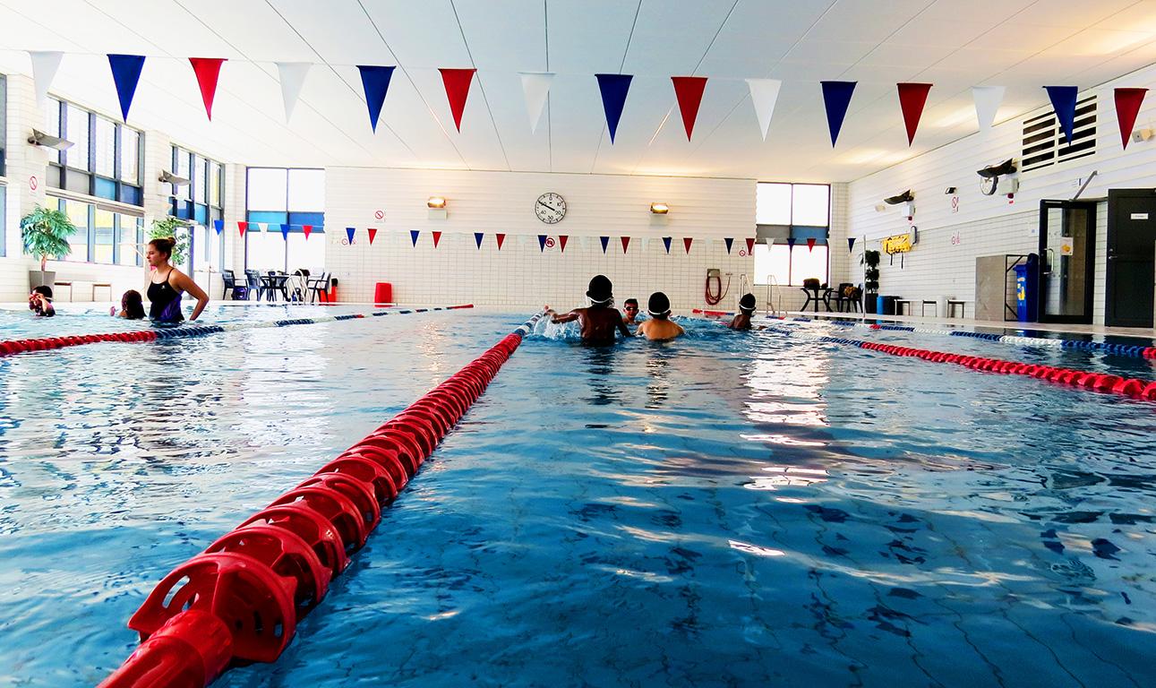 Barn simmar i bassäng.