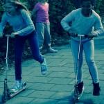 Två elever åker iväg på sparkcyklar.