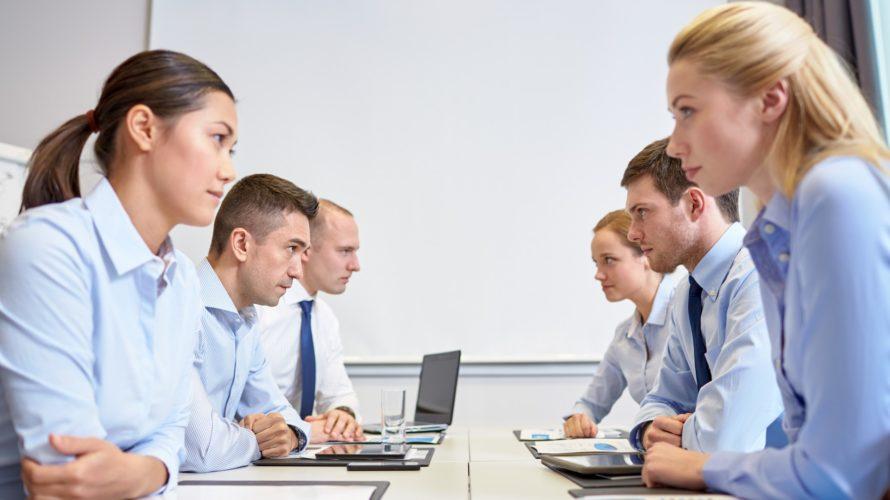 Människor sitter mittemot varandra och stirrar irriterat på varandra.