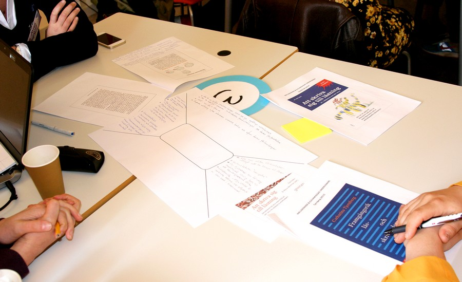 Papper ligger i mitten av bod med anteckningar på.