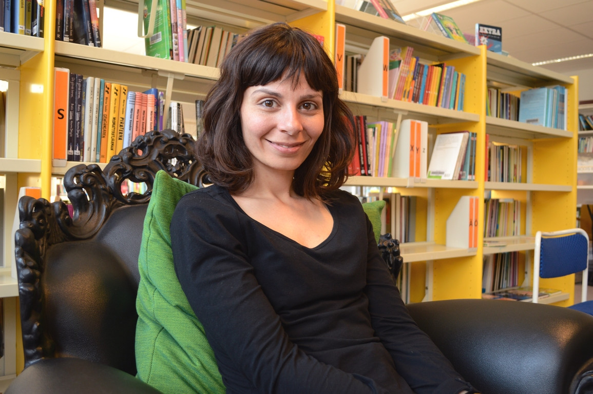 Kvinna sitter i bibliotek.