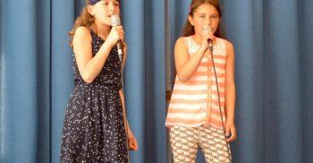 Två elever sjunger i mikrofoner.