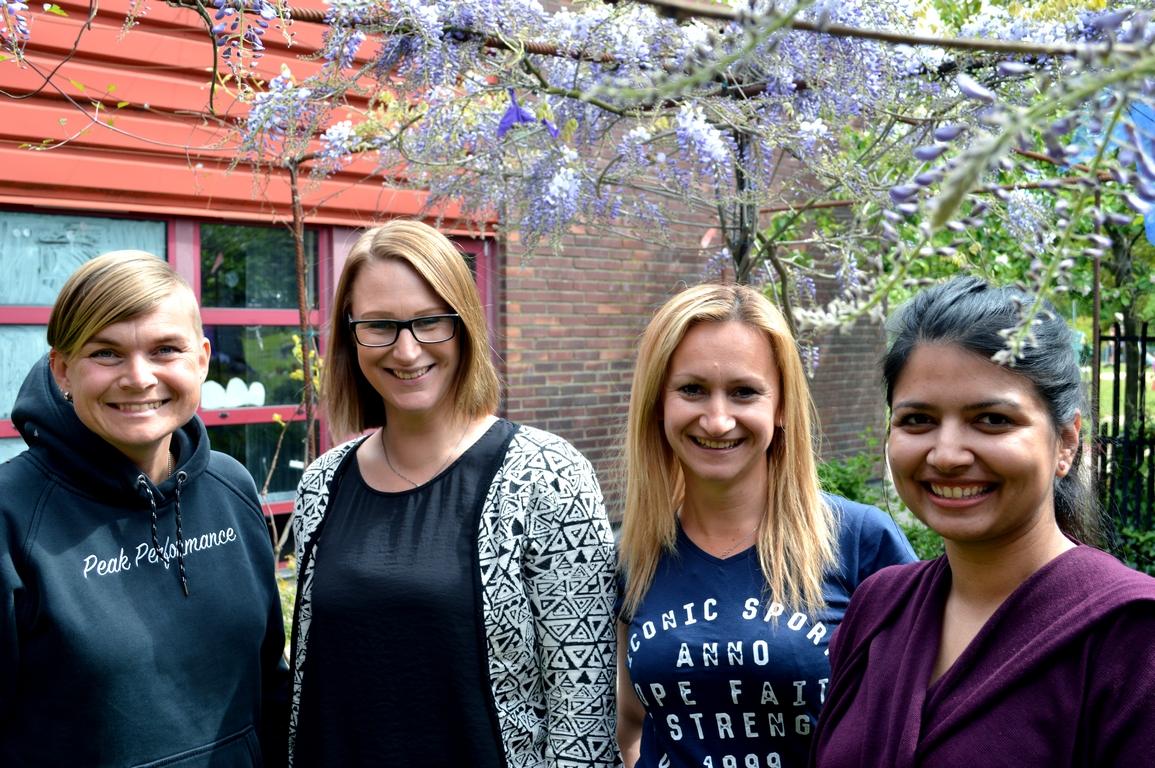 Fyra personer står under ett blommande träd.