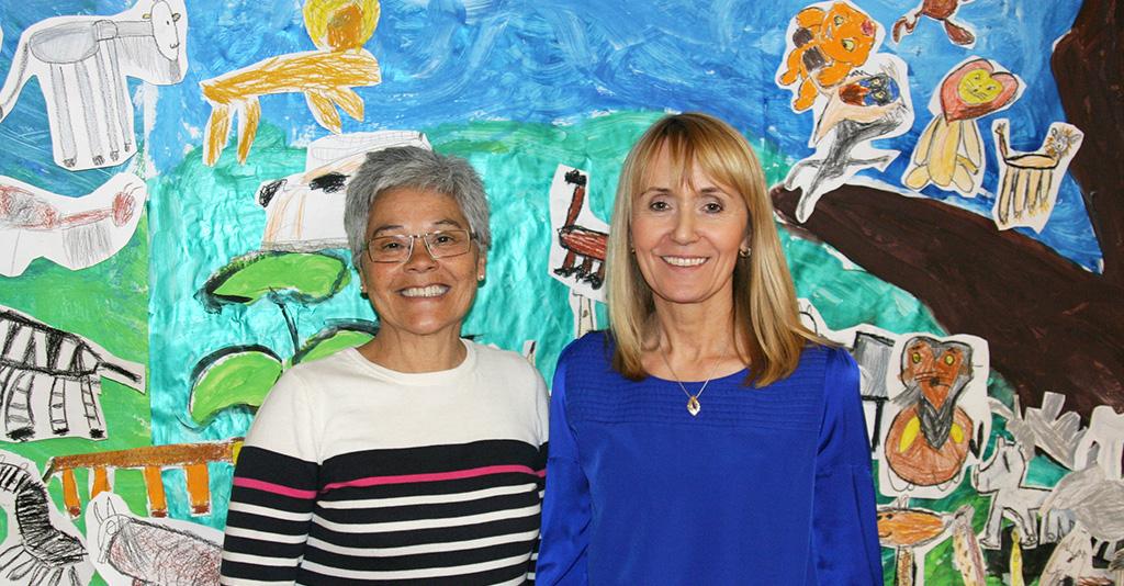 Estela Garcia & Bozena Kondrat står framför barns teckningar.