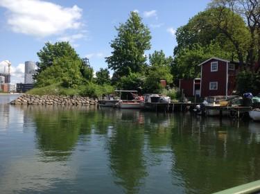 Båtar ligger förtöjda vid röd stuga.