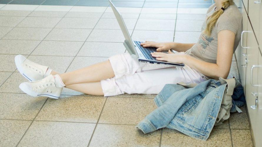 Flicka sitter lutad mot skåp med dator i knäet.