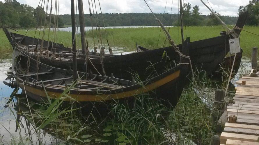 Två vikingabåtar ligger förtöjda vid en brygga.