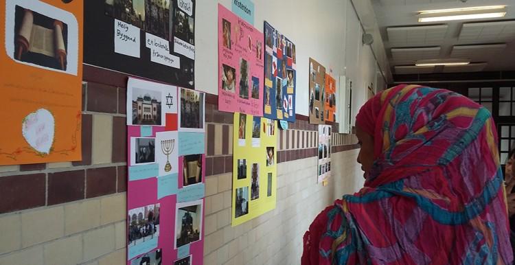 Kvinna tittar på planscher i skolans korridor.