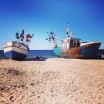 Två rostiga båtar ligger på en sandstrand.