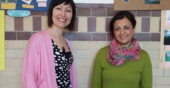 Två kvinnliga lärare står framför planscher som är uppsatta på en vägg.
