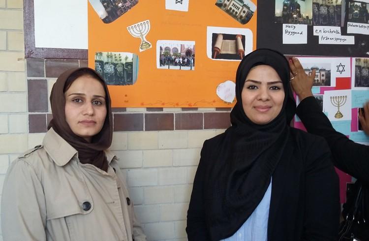 Två kvinnor framför en plansch som beskriver judendom.