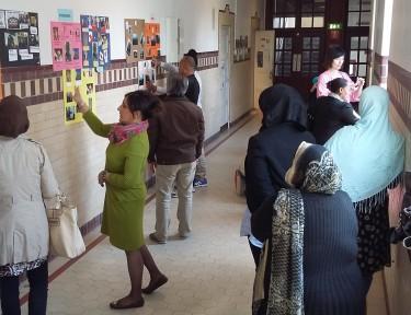 Pedagog och elever tittar på uppsatta planscher i skolans korridor.