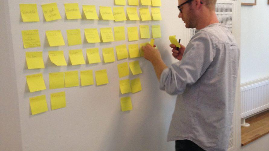 Björn Reisnert sätter upp post itlappar på väggen.