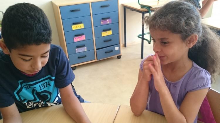 Två barn sitter i klassrum.
