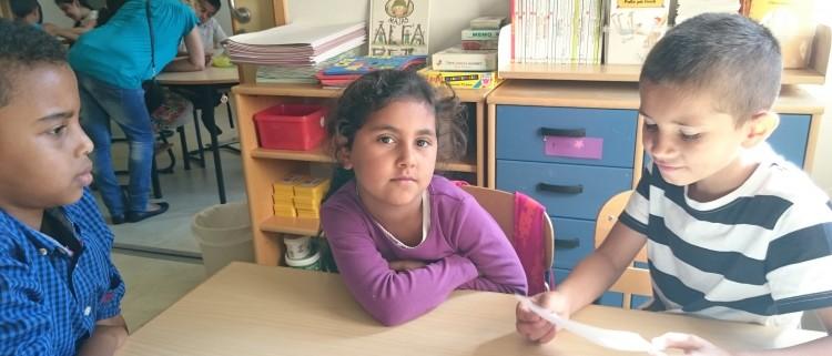 Tre barn sitter i klassrum.