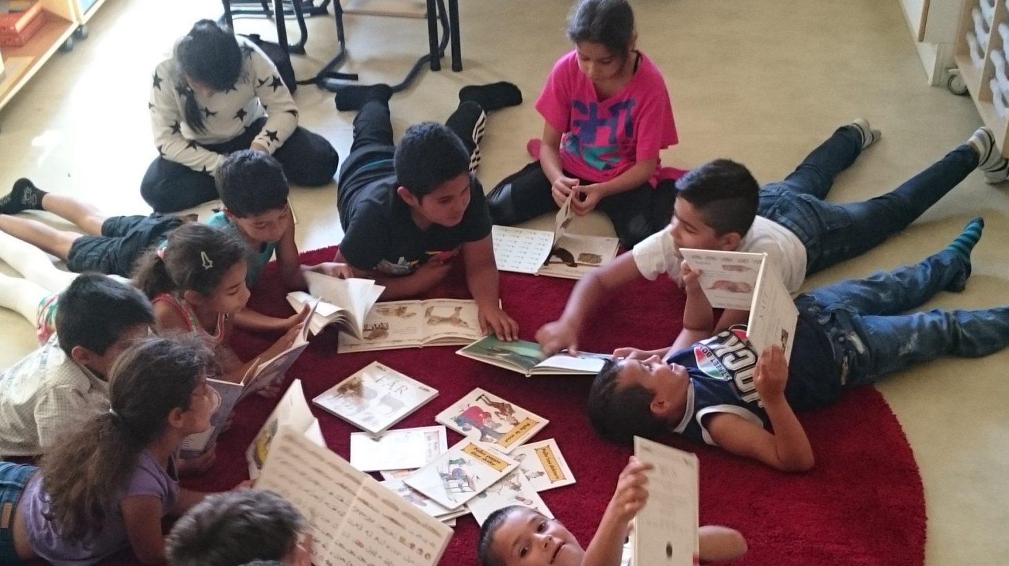 Barn sitter och ligger på golvet och läser.