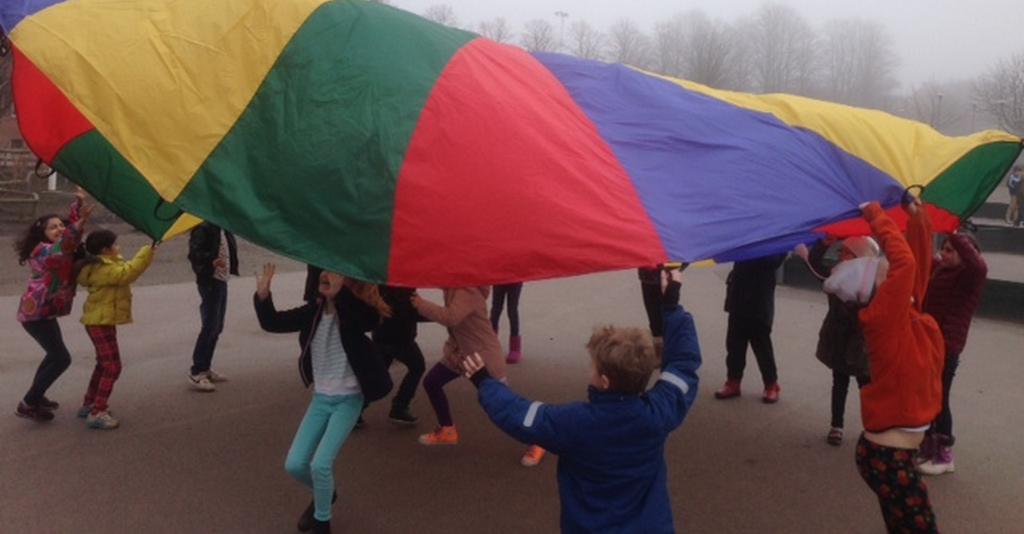 Barn leker med färgglad fallskärm.