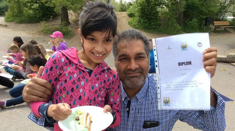 Flicka äter tårta och man håller om henne och håller upp diplom.
