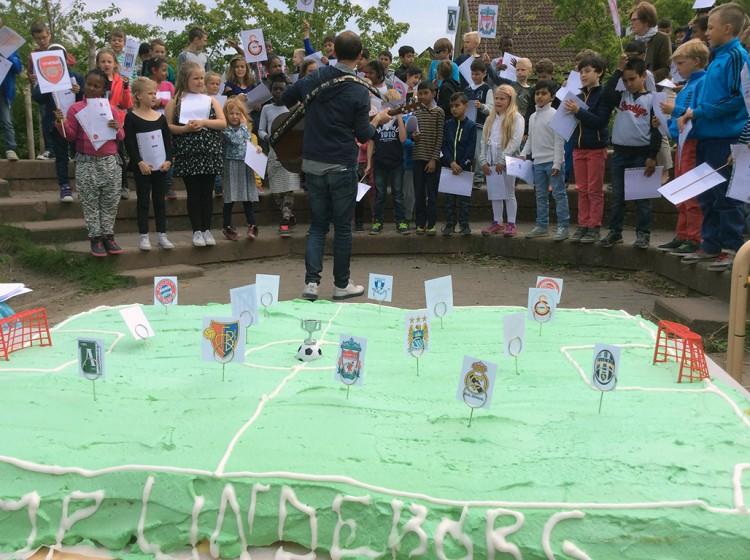 Elever framför jättestor tårta formad som fotbollsplan.