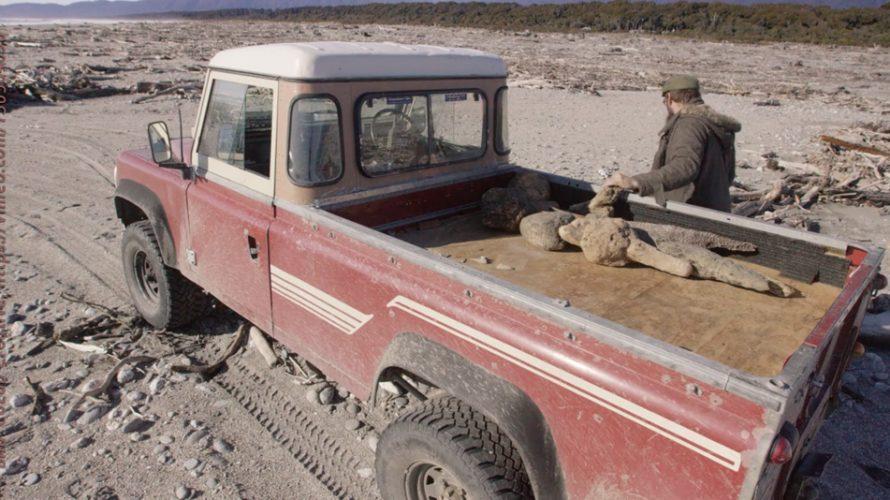 Gammal jeep står i stenlandskap.