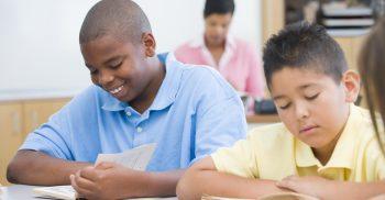 Två elever läser i bok.