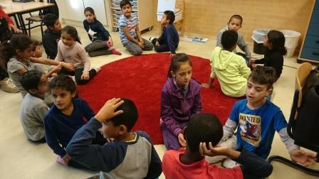 Barn sitter och pratar på golvet i en cirkel.