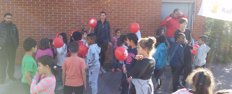 Barn håller upp röda ballonger.